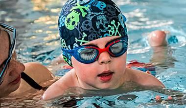 """Dzieci początkujące w wieku od dwóch do pięciu lat uczestniczą w zajęciach wraz z rodzicem lub opiekunem dzięki czemu czują one się w wodzie komfortowo. Podczas nauki pływania dziecko + rodzic w wodzie łączymy zalety lekcji indywidualnych i grupowych co przyspiesza proces nauczania prawidłowej techniki pływania. Rodzice pomagają maluchom utrzymać właściwą sylwetkę w wodzie, oraz umożliwiają wykonanie przez dziecko bardziej złożonych ćwiczeń niezbędnych w rozwijaniu techniki pływania stylem dowolnym – """"kraulem"""", grzbietowym i klasycznym – """"żabka"""". Nasze zajęcia to także dodatkowy czas, który rodzice mogą aktywnie spędzić z ich pociechami."""